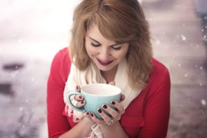 Woman holding the cup in hands smelling the coffee aroma
